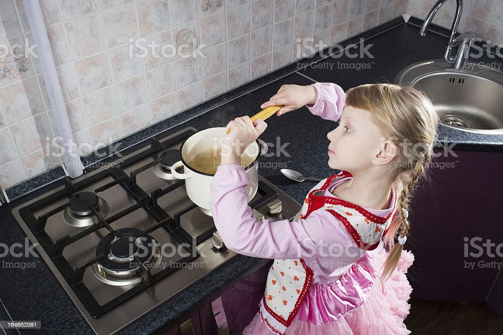 little girl putting pasta in the pot royalty-free stock photo
