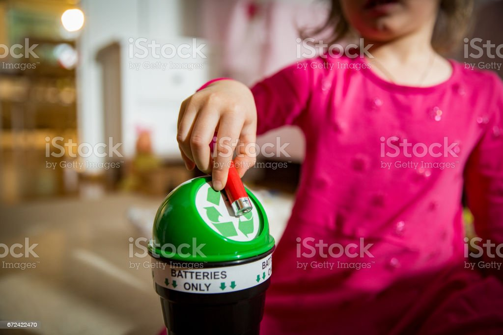 Little girl putting used batteries into recycling box stock photo
