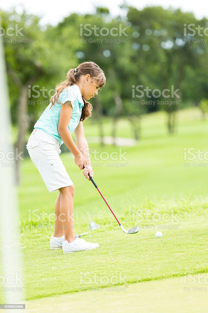 Little girl putts ball at golf course stock photo