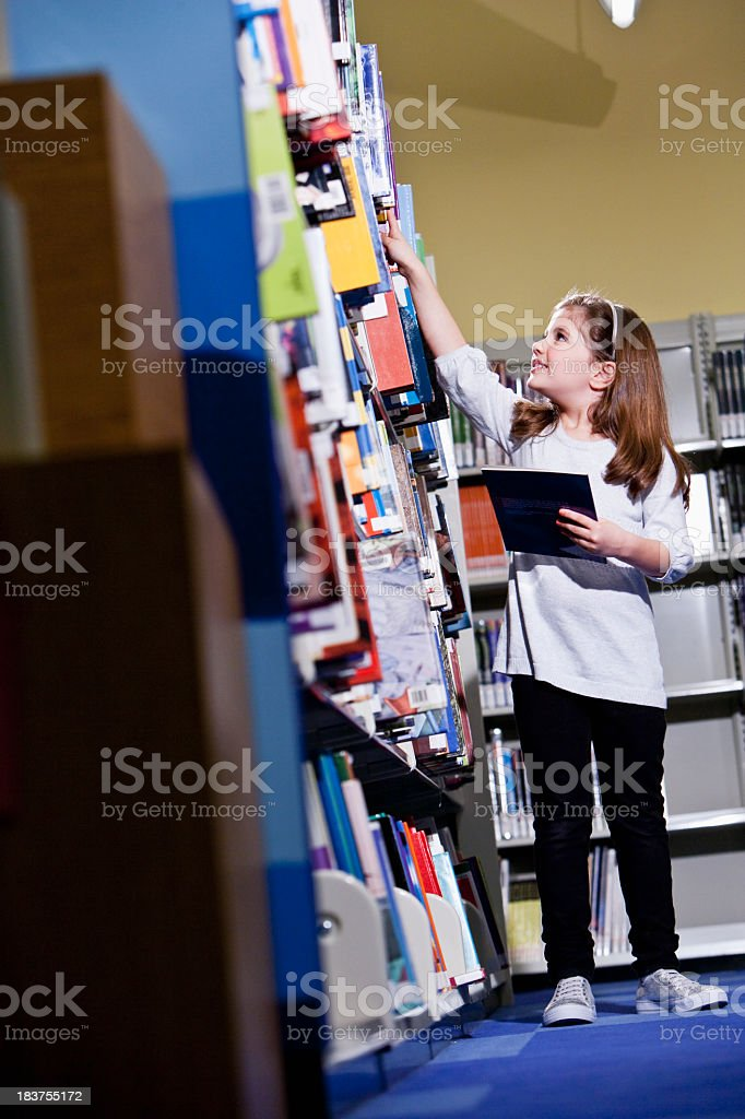 Little girl reaching for book on library bookshelf stock photo
