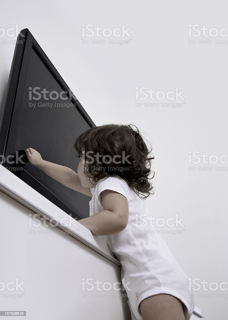 Little girl reaching up to touch the TV stock photo