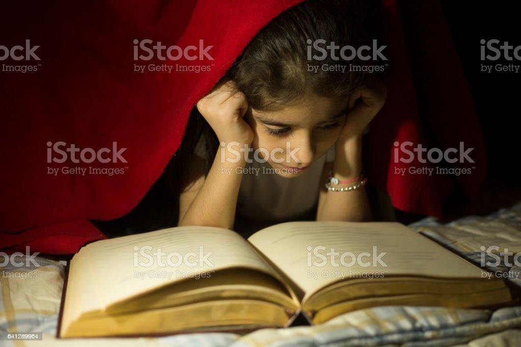 Little girl reading a book in bed stock photo