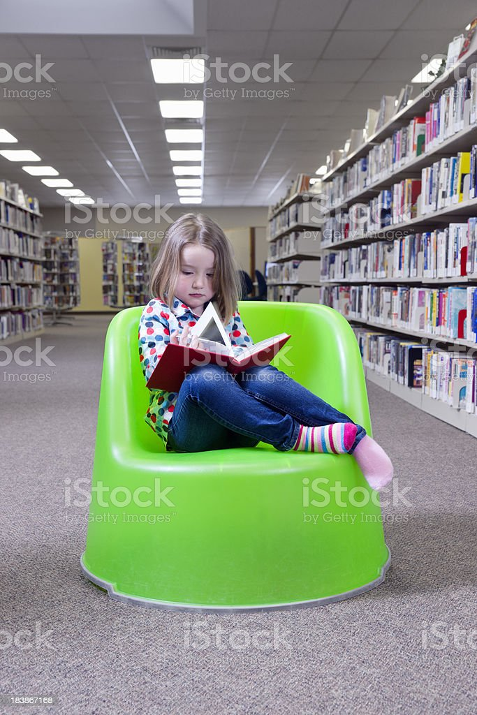 Little girl reading a book in the library royalty-free stock photo