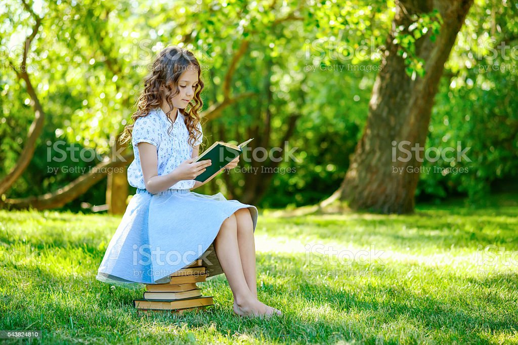Little girl reading a book stock photo