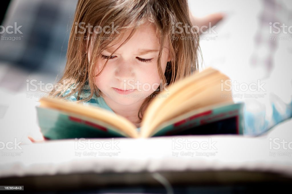 Little Girl Reading Book on Hammock Outside stock photo