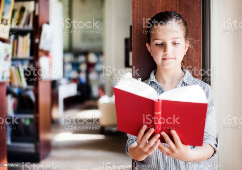 Little Girl Reading in a Library royalty-free stock photo