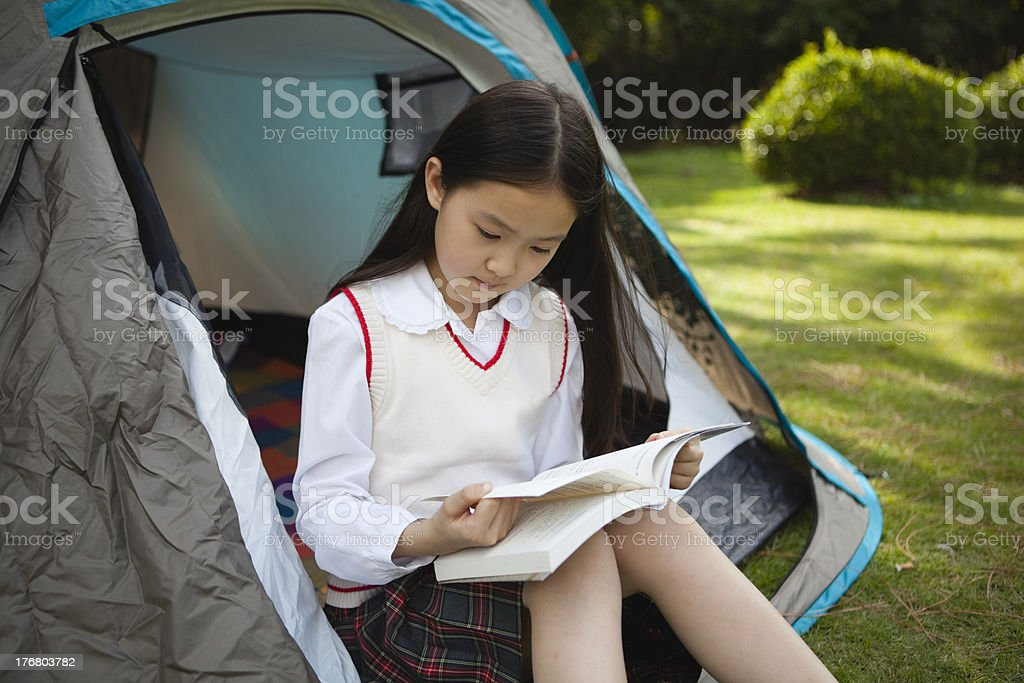 little girl reading in a tent royalty-free stock photo