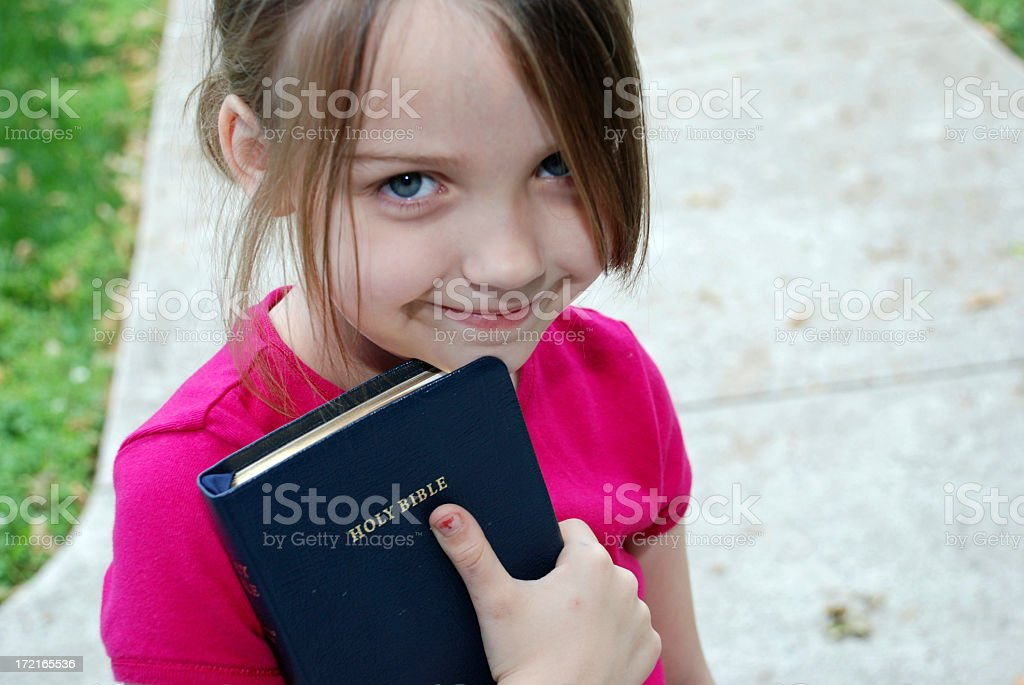A little girl reading the holy bible stock photo