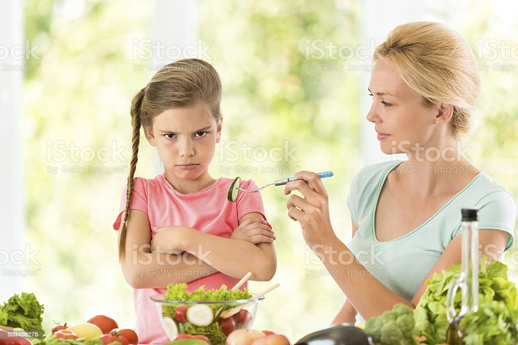 Little girl refuses to eat vegetables stock photo