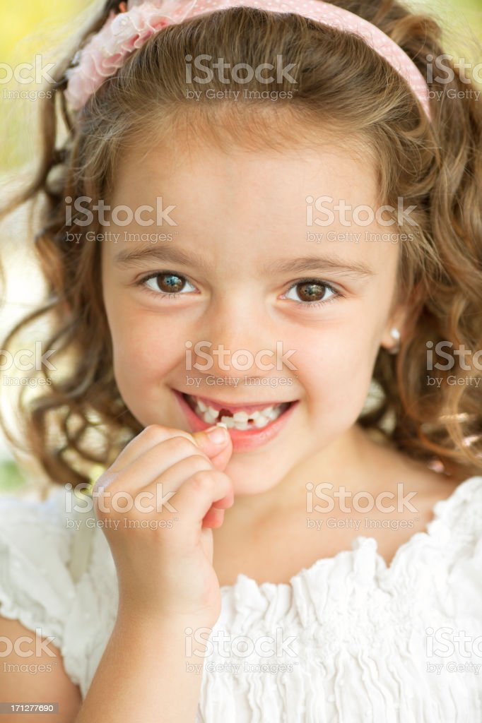 Little Girl Removing Tooth stock photo