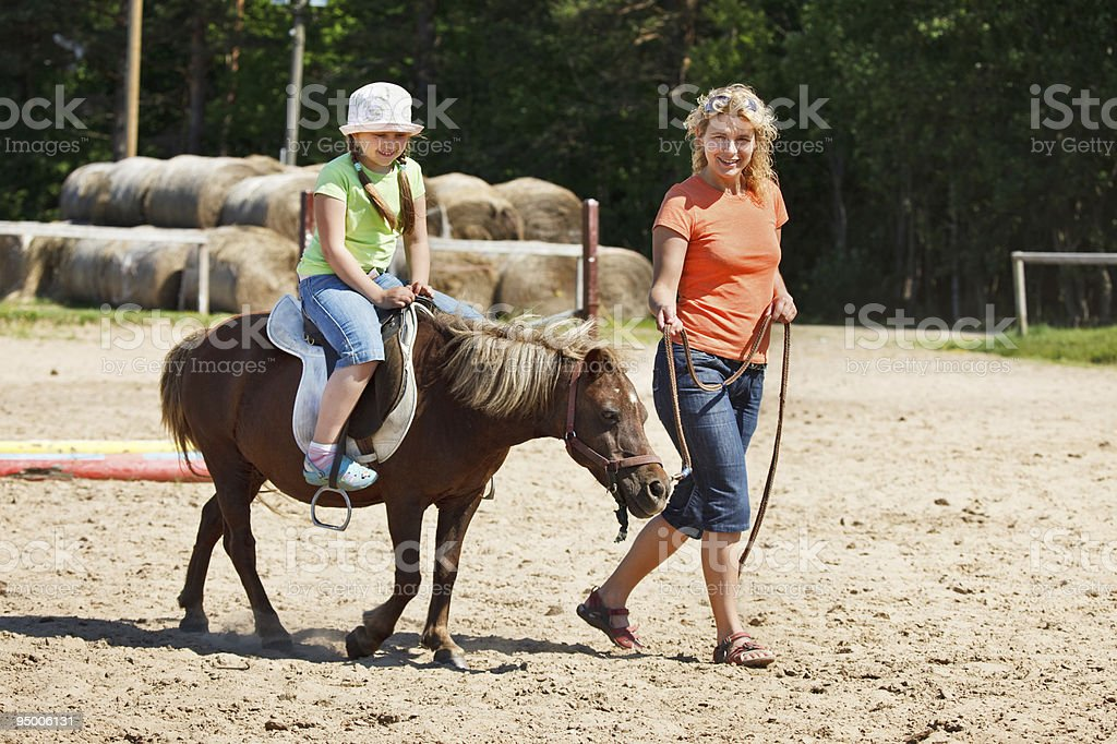 A little girl riding a pony while a woman guides it stock photo