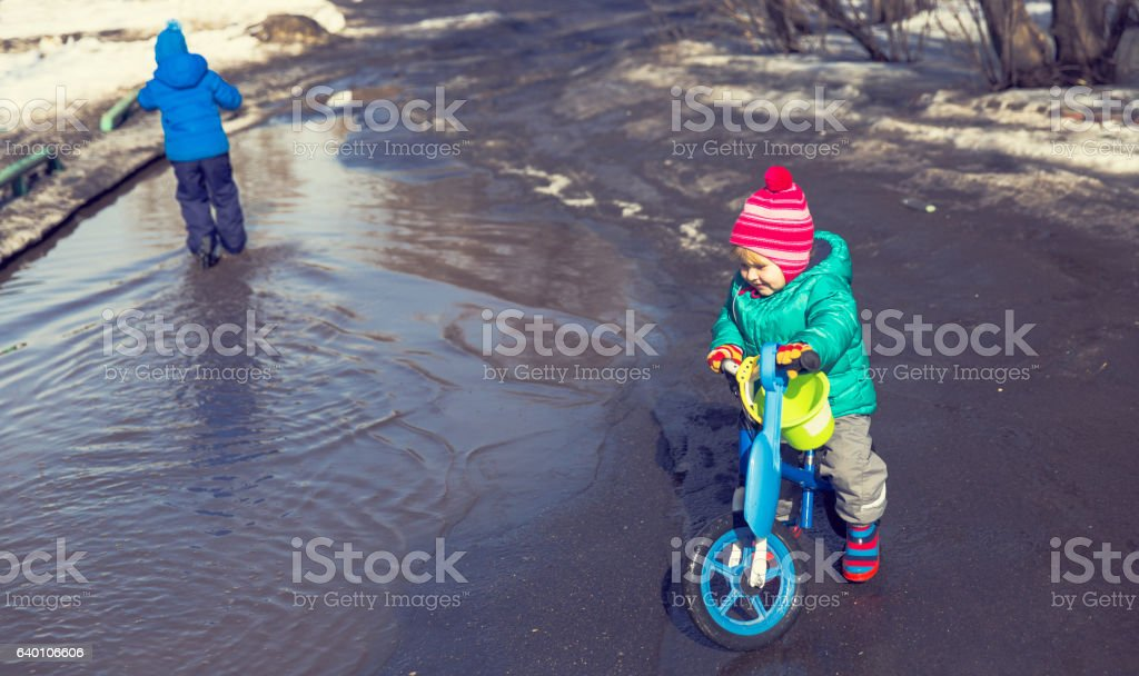 little girl riding bike and boy on scooter playing in stock photo