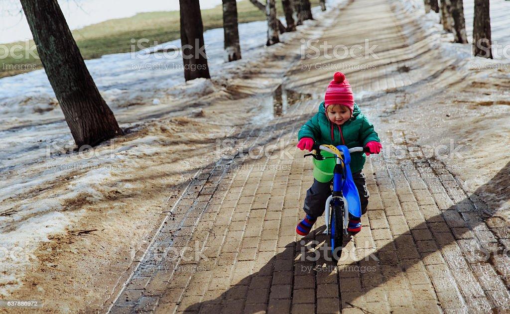 little girl riding bike in winter or spring stock photo