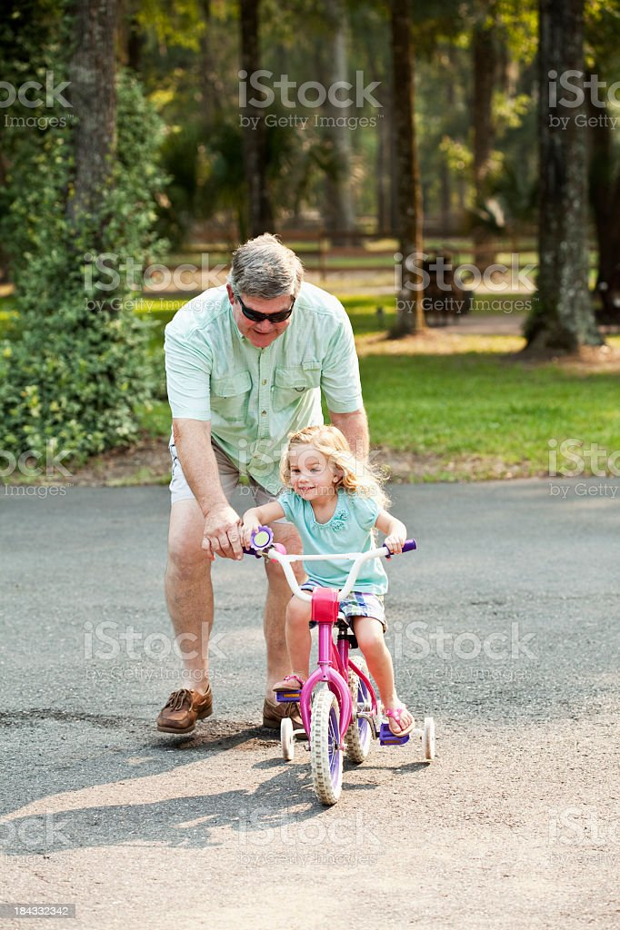 Little girl riding bike with grandfather stock photo