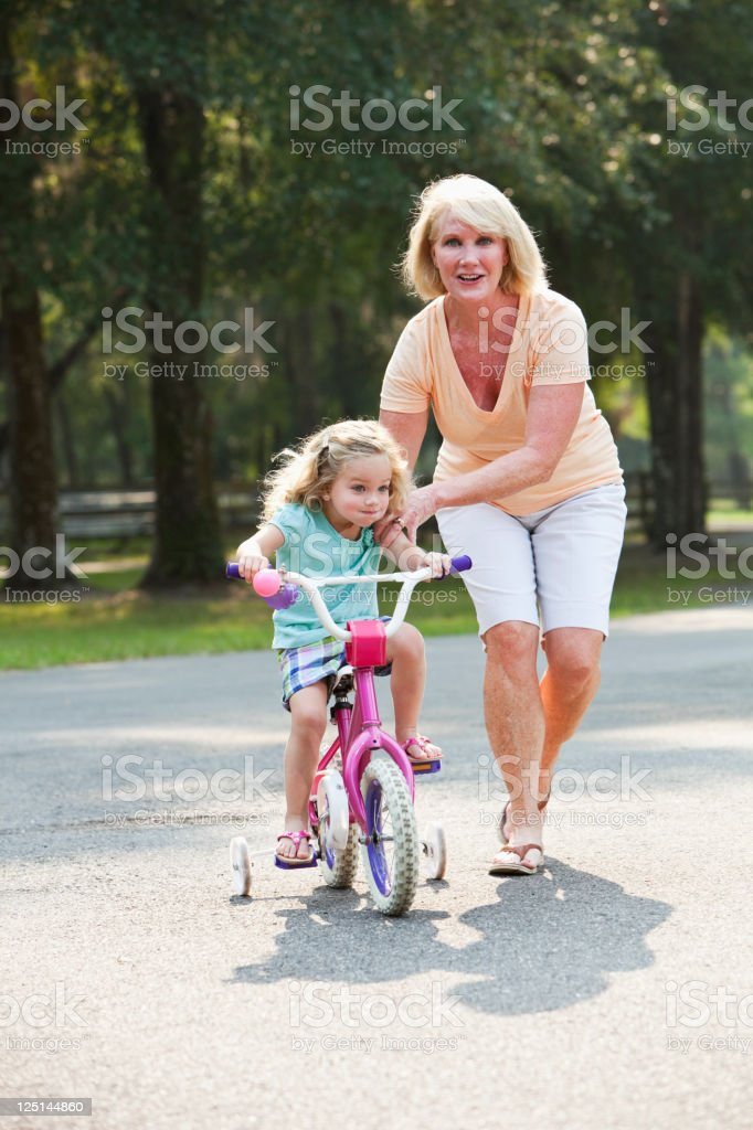Little girl riding bike with grandmother stock photo