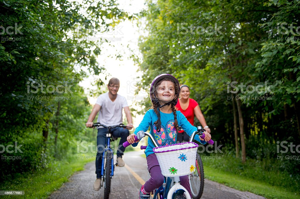 Little Girl Riding Bike with her Parents stock photo