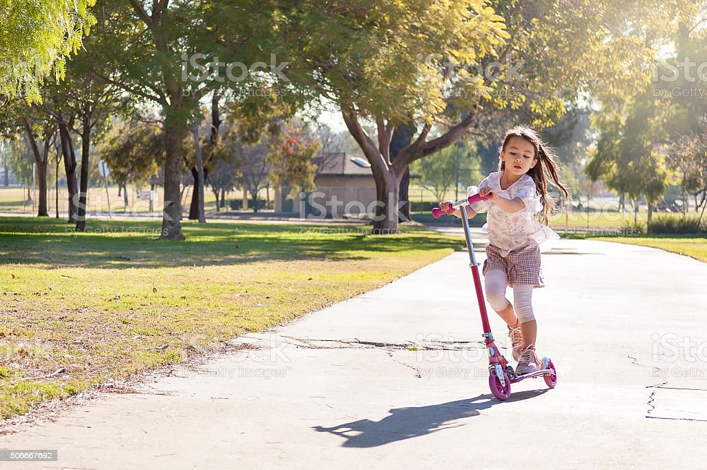 Little girl riding her scooter in the park stock photo