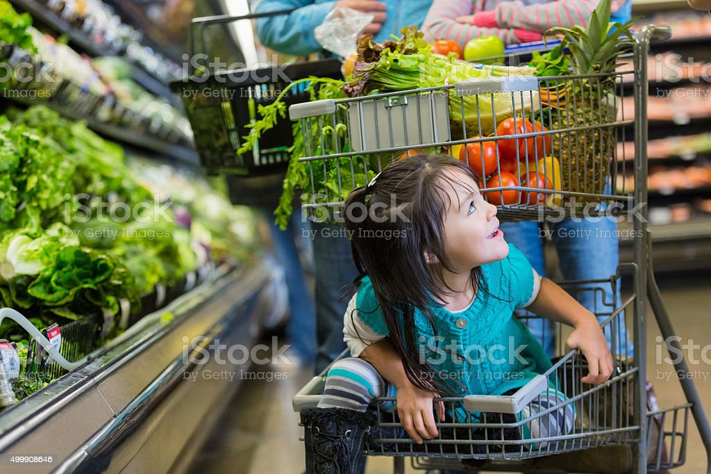 Little girl riding in bottom basket of supermarket shopping cart stock photo
