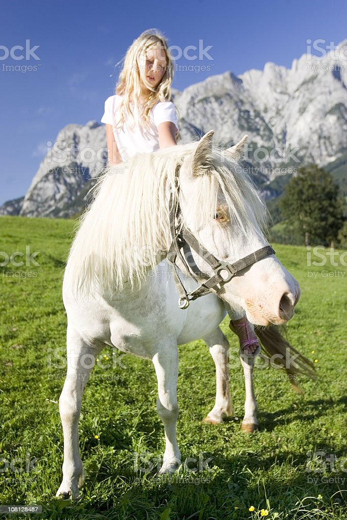 Little Girl Riding Pony in Austrian Alps Meadow royalty-free stock photo