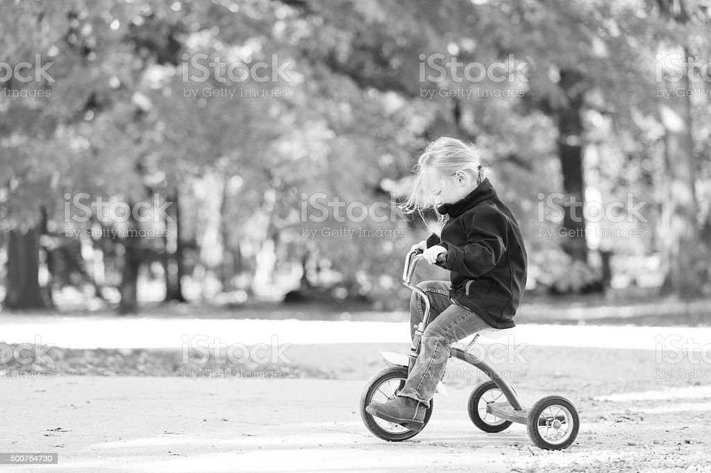 Little Girl Riding Tricycle stock photo