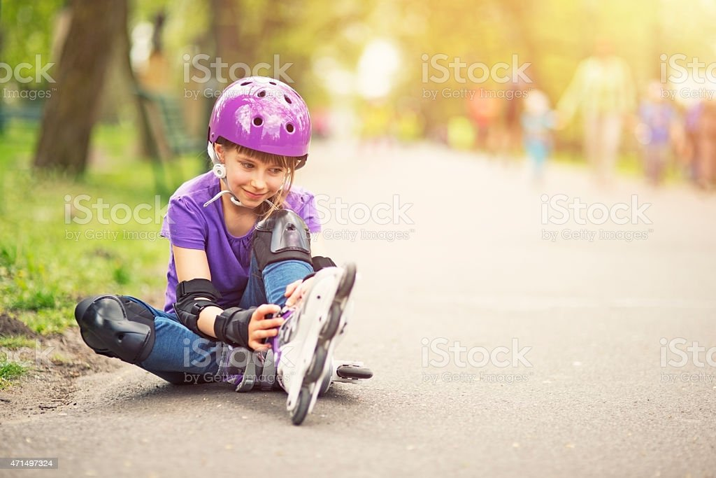 Little girl rollerskating in park stock photo