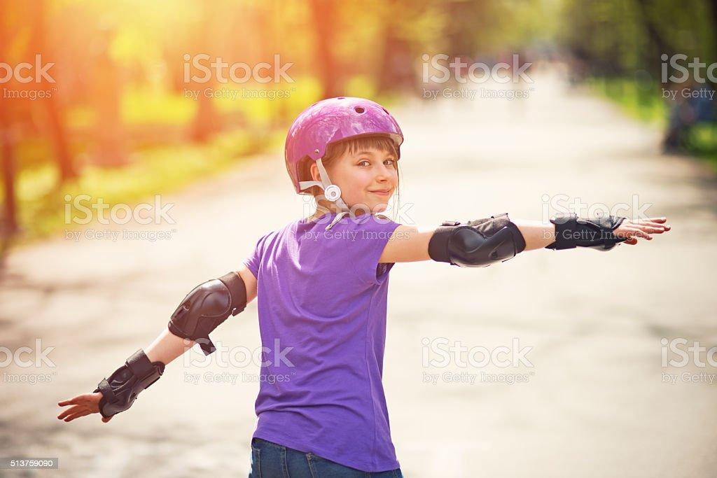 Little girl rollerskating in park stock photo