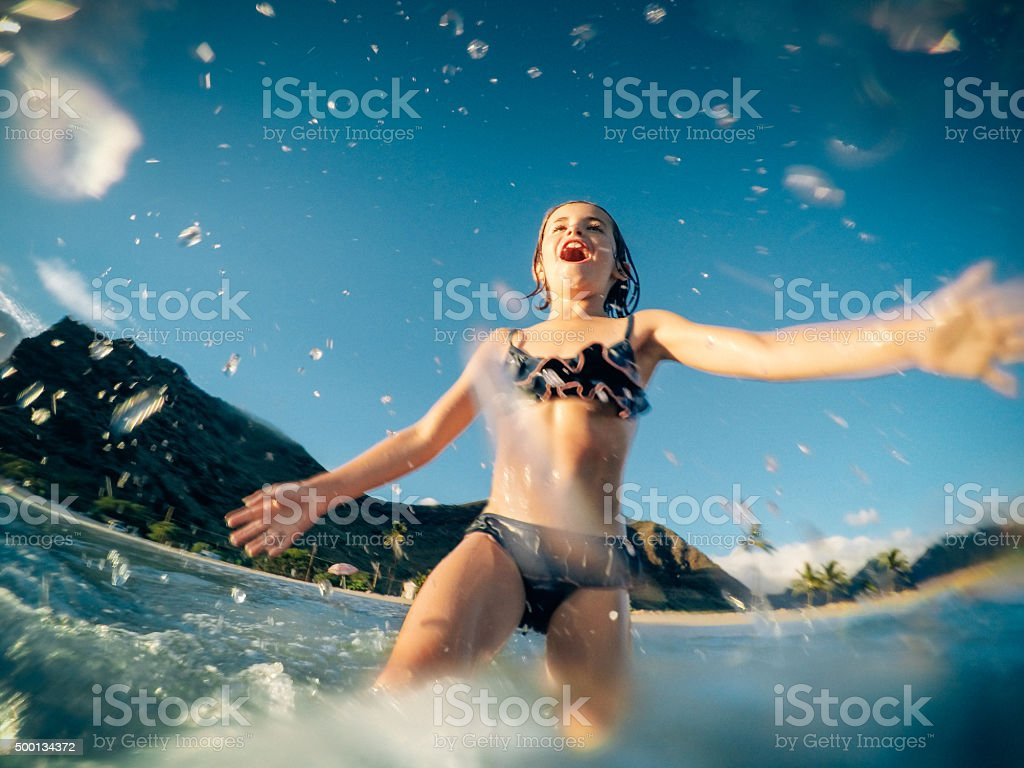 Little Girl Running Against the Waves in Hawaii stock photo