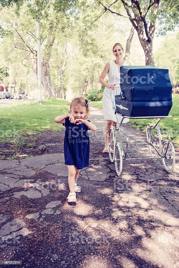 Little girl running away from mother while walking in park. stock photo