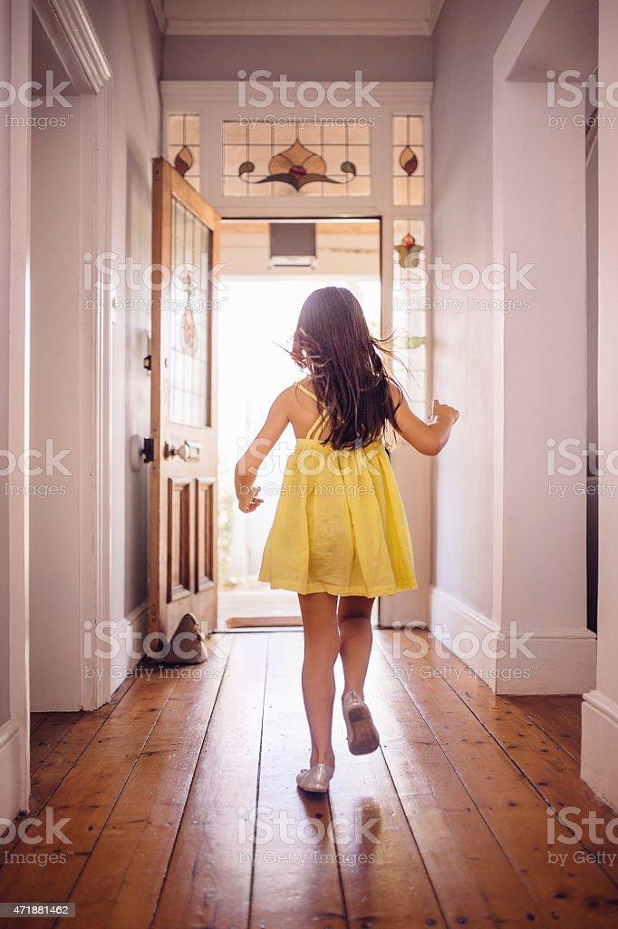 Little girl running happily to an open front door stock photo