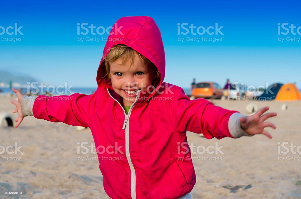 Little girl running  near the camping tents on the sea stock photo