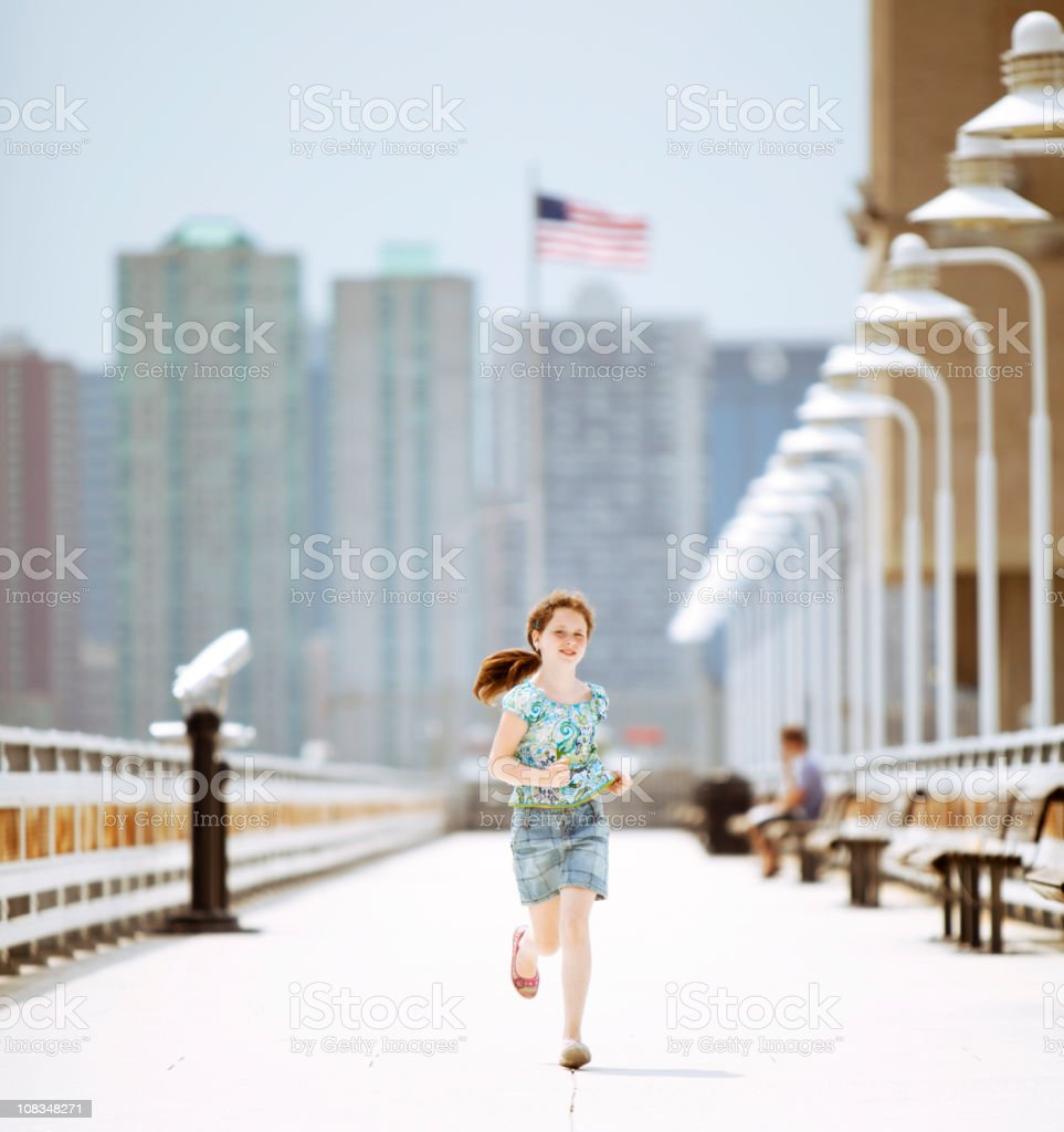 Little girl running on a pier towards the camera. stock photo