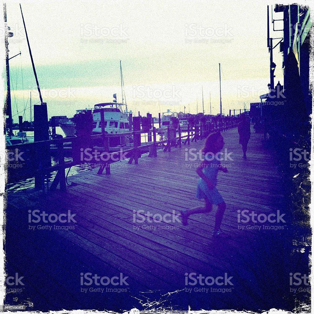 Little girl running on embankment of Beaufort in the evening. stock photo