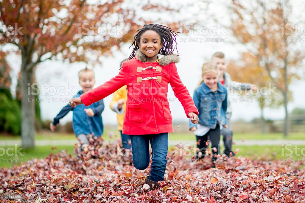 Little Girl Running Through a Leaf Pile stock photo