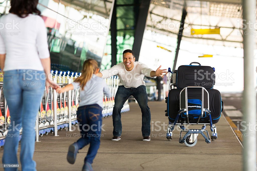 little girl running to her father at airport stock photo