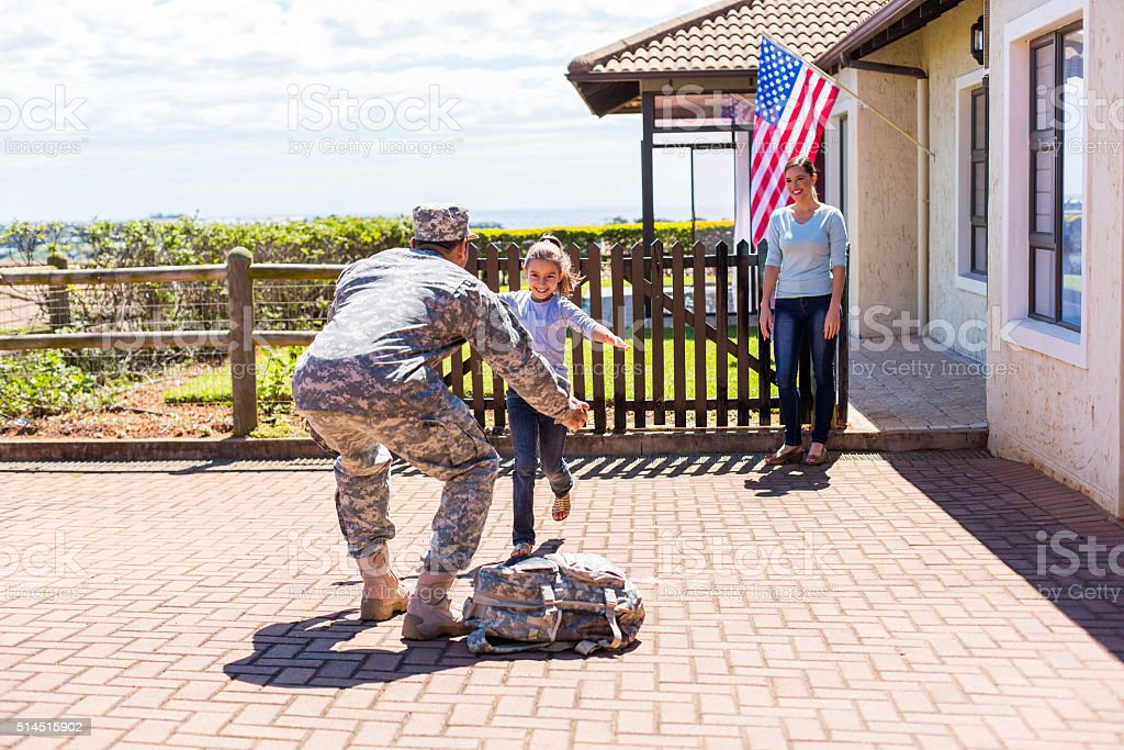 little girl running to her military father stock photo