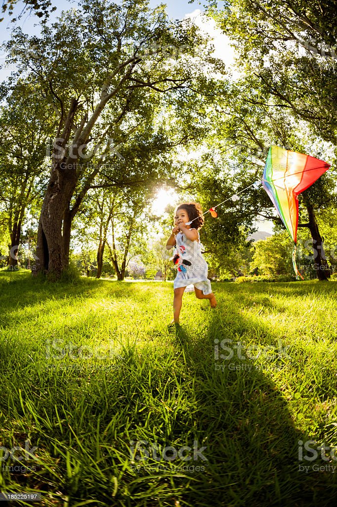 Little Girl Running With a Kite In Garden stock photo