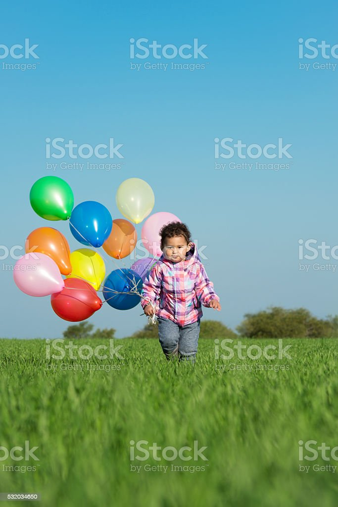 Little girl running with balloons in hand. stock photo