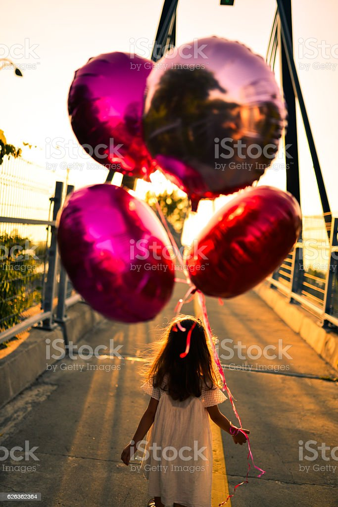 little girl running with balloons on a bridge at sunset stock photo