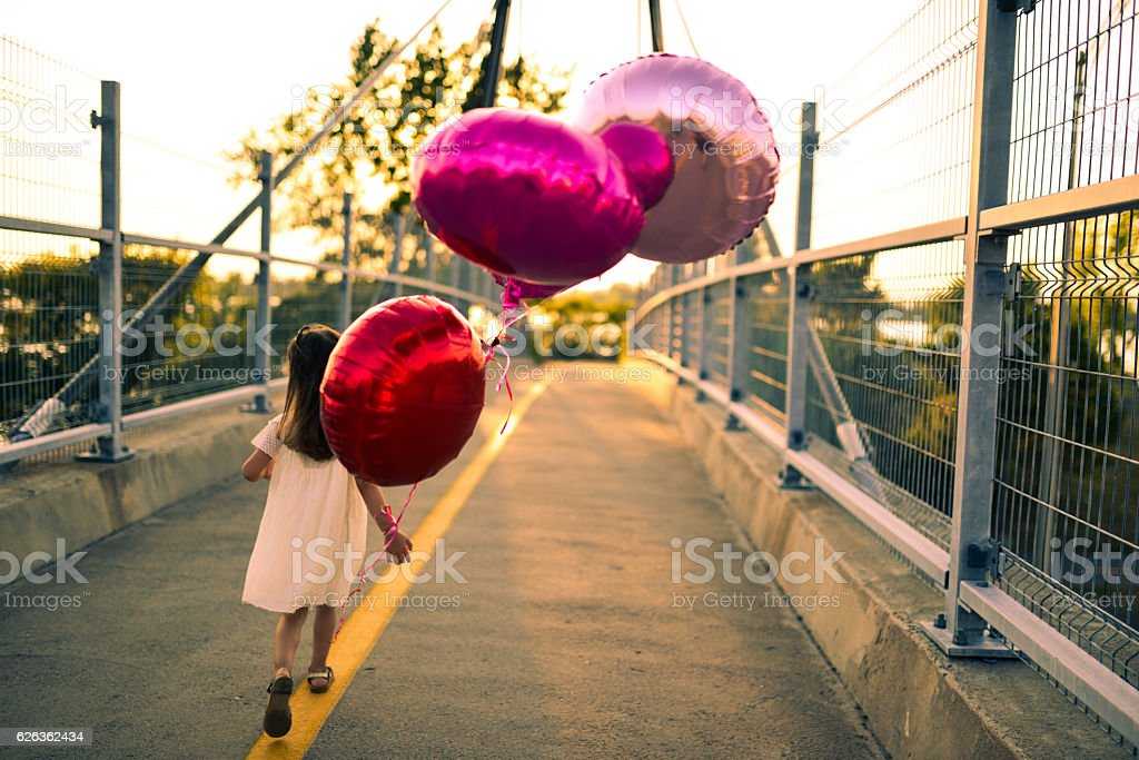 little girl running with balloons on a bridge at sunset stock photo