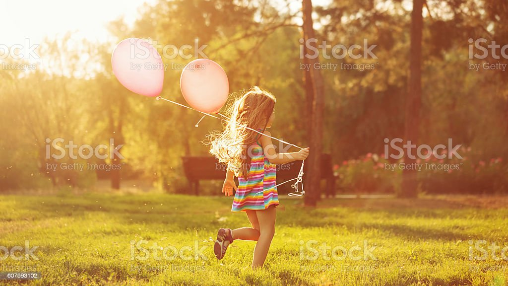 Little girl running with balloons stock photo