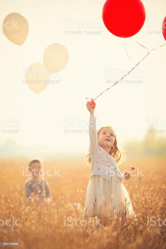 Little girl running with balloons stock photo