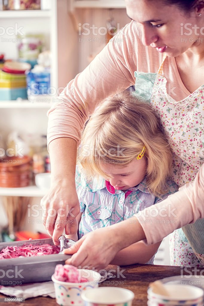 Little Girl Scooping Homemade Strawberry Ice Cream with her Mother stock photo
