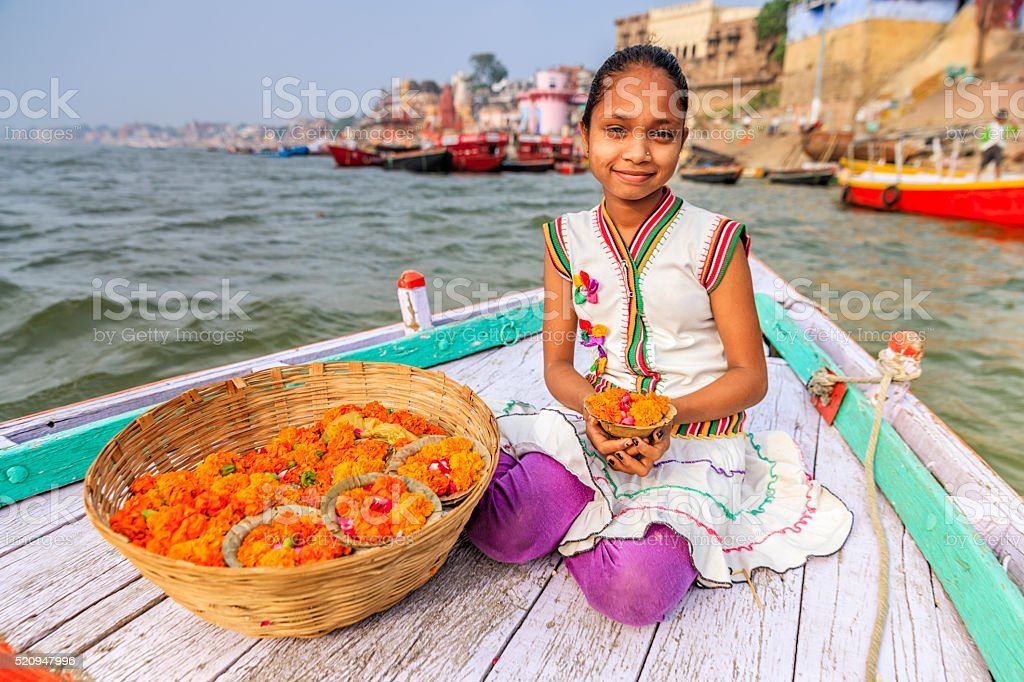 Little girl selling flower candles in boat, Ganges River, Varanasi stock photo
