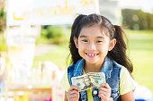 Little girl sells lemonade in front of her house