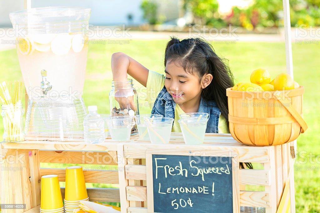 Little girl sells lemonade in her front yard stock photo