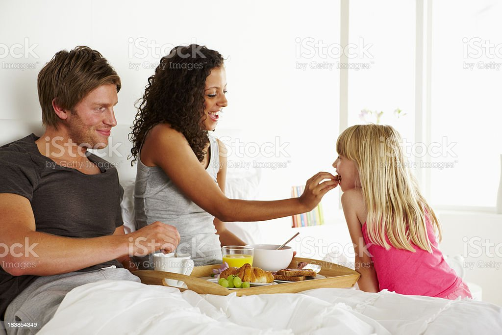 Little girl serves breakfast to her parents - Morning royalty-free stock photo