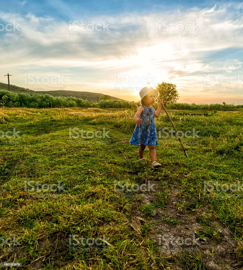 Little girl shepherd with her staff lost her lambs stock photo