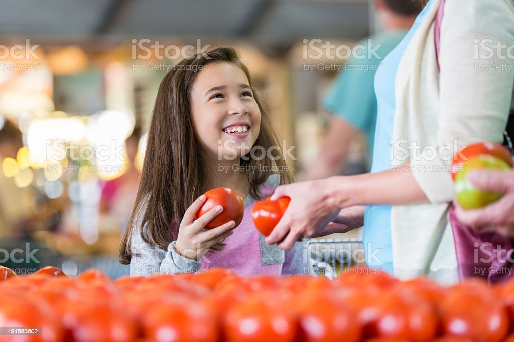 Little girl shopping for produce at market with mother stock photo