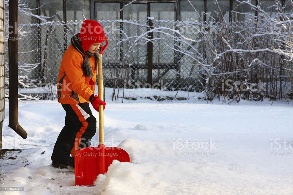 Little girl shoveling snow with shovel stock photo
