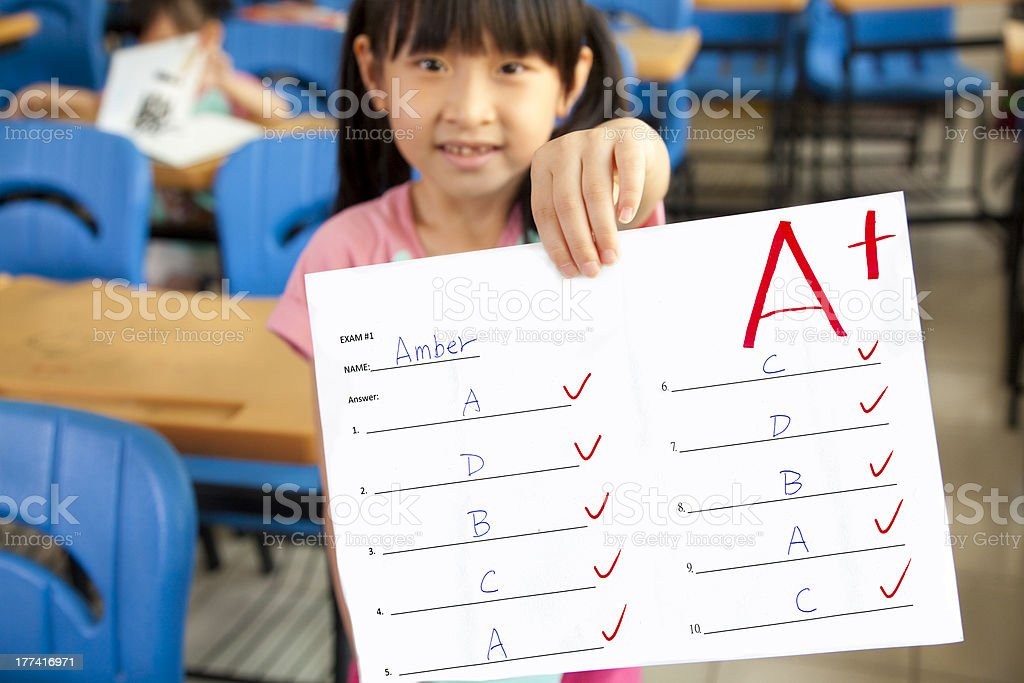 little girl showing exam paper stock photo